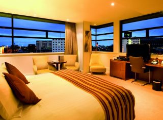 Bedroom with a panoramic view at dusk at Macdonald Manchester Hotel & Spa